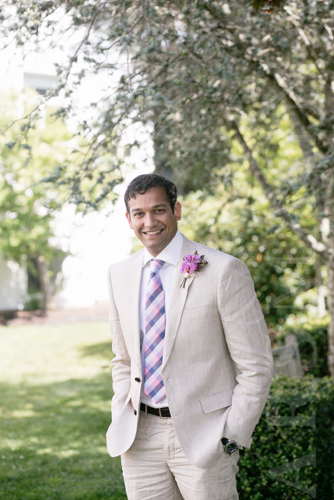Groom in linen suit and pink and purple madras tie.