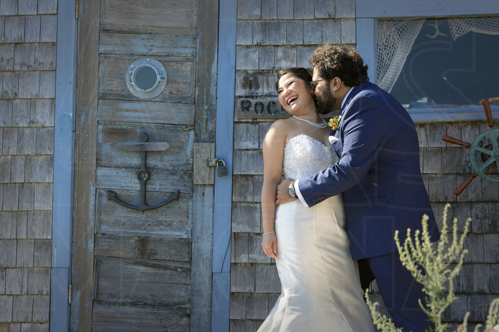 bride and groom wedding at the Shalin Liu Performance Center in Rockport kissing on Bearksin Neck Wharf
