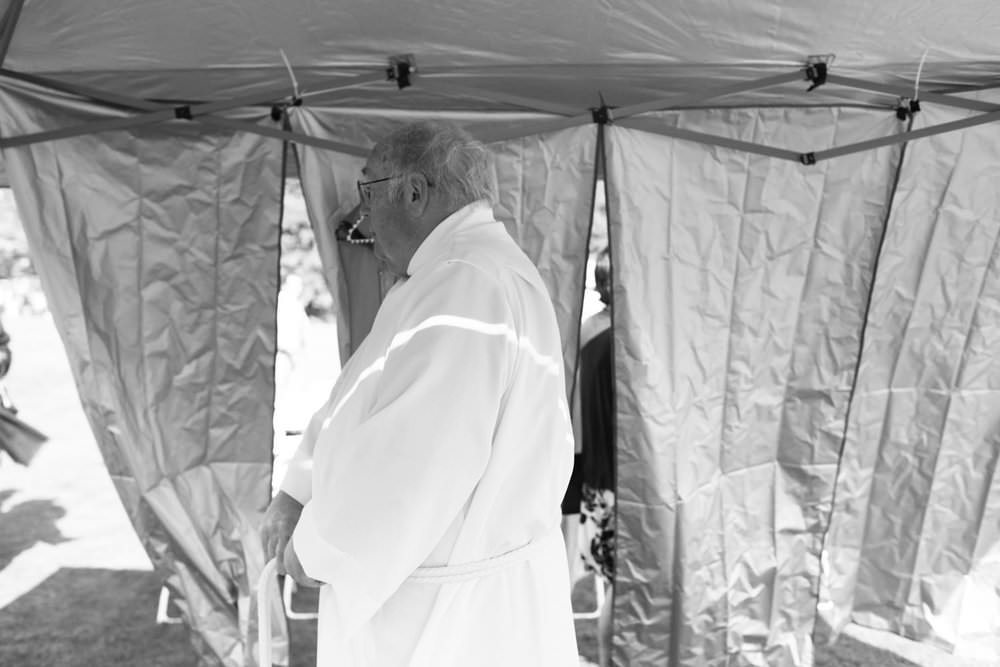 bride's childhood pastor getting ready before the outdoor ceremony at settlers crossing lunenberg wedding