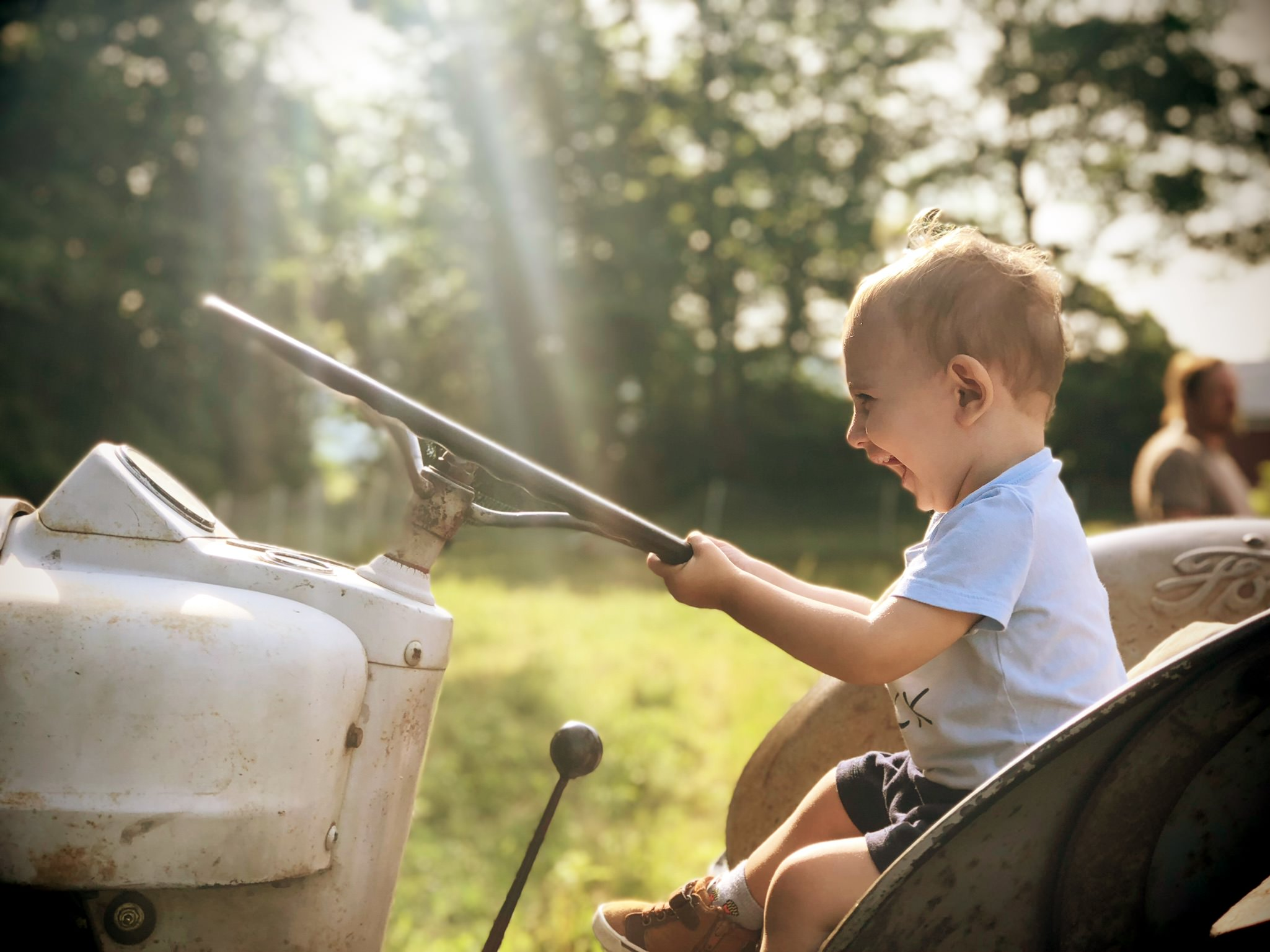 ecstatic toddler driving tractor